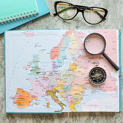 Map of Europe with compass, notebooks, eyeglasses, on a stone countertop