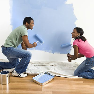 Painting couple with rollers on a blue wall