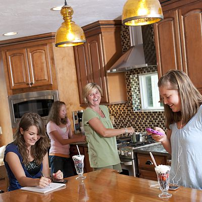 Lori O'Driscoll cooking, with children hanging out in the new kitchen