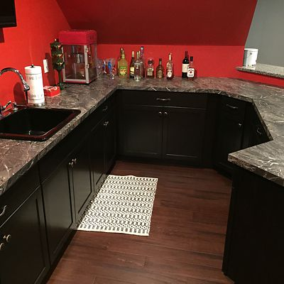 Black cabinetry in home sports bar designed by Josh Simmons