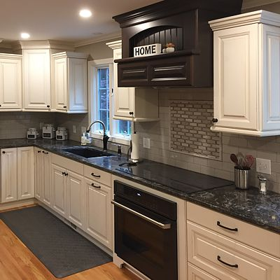 Stove area accented with dark cabinetry range hood in kitchen with white cabinetry designed by Josh Simmons