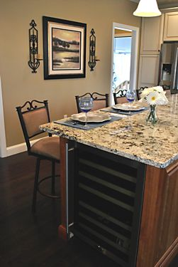 Granite island eating area in Wrentham, MA kitchen designed by Jamie Thibeault