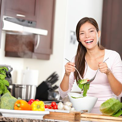 Woman tossing salad in kitchen