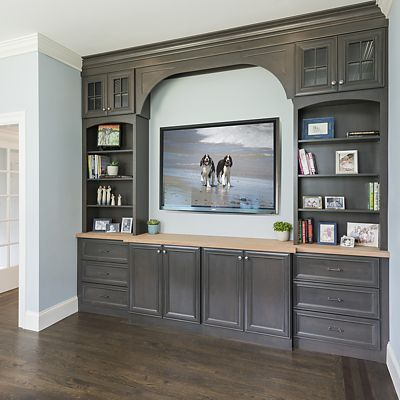 Built-in entertainment center with a mixture of closed storage, open shelves, and display cabinets, surrounding the large space for a flat screen television